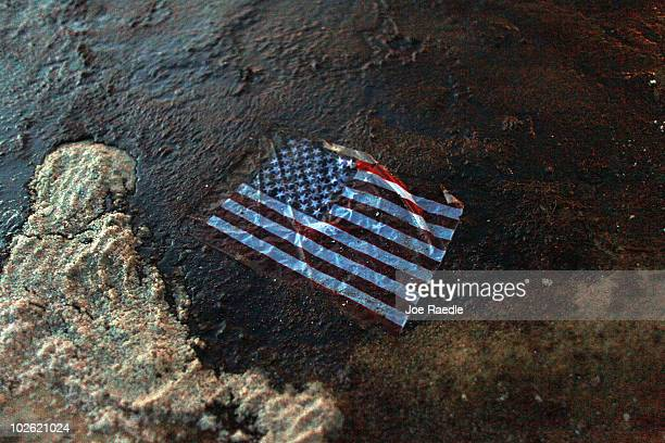 An American flag lays in a slick of oil that washed ashore from the Deepwater Horizon oil spill in the Gulf of Mexico on July 4 2010 in Gulf Shores...