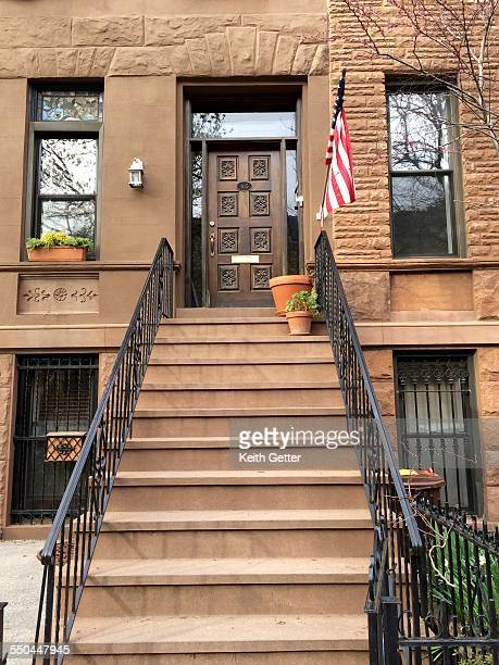 An American Flag on a residential flagpole suspended from the facade of a brownstone townhouse over the stoop in the historic landmark district of...