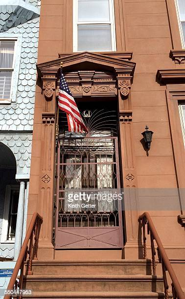 An American Flag on a residential flagpole suspended over the front door and stoop of a brownstone building in Fort Greene Brooklyn New York City...