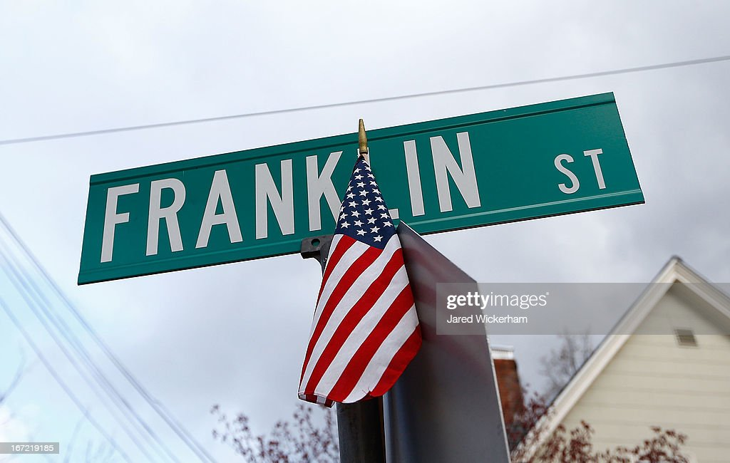 An American flag sits atop the Franklin Street sign while many different members of law enforcement investigate the scene on April 22, 2013 in Watertown, Massachusetts. A manhunt ended for Dzhokhar A. Tsarnaev, 19, a suspect in the Boston Marathon bombing after he was apprehended on a boat parked on a residential property in Watertown, Massachusetts. He has been charged with one count of using a weapon of mass destruction and one count of malicious destruction of property by means of an explosive device resulting in death. His brother Tamerlan Tsarnaev, 26, the other suspect, was shot and killed after a car chase and shootout with police. The bombing, on April 15 at the finish line of the marathon, killed three people and wounded at least 170.