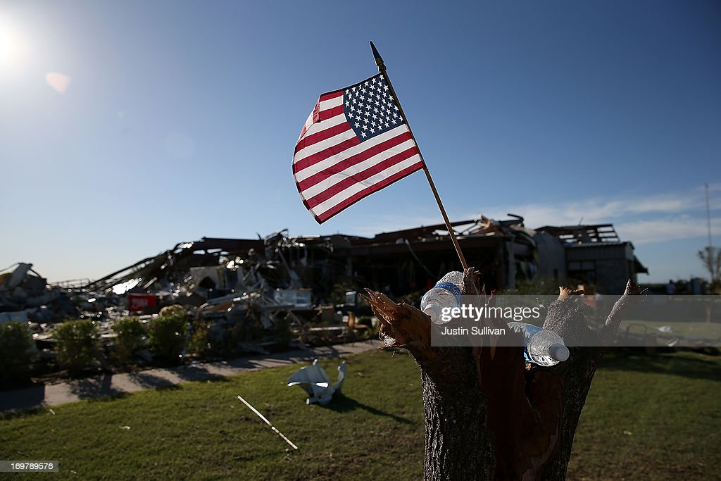 An American flag sits in a tree stump outside of a restaurant the was damaged by a series of tornadoes that ripped through the area a day earlier on June 1, 2013 in El Reno, Oklahoma. A series of tornadoes ripped through the area on Friday evening killing at least nine people, injuring many others and destroying homes and buildings.