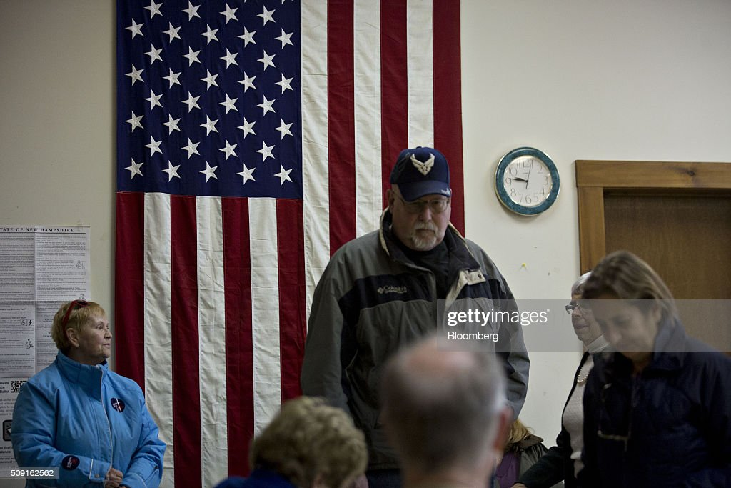 An American flag stands behind residents lined up to receive ballots at the Bartlett town hall during the first-in-the-nation New Hampshire presidential primary in Bartlett, New Hampshire, U.S., on Tuesday, Feb. 9, 2016. Polls suggest that Donald Trump maintains a dominant lead against his Republican rivals in New Hampshire ahead of today's primary. Photographer: Andrew Harrer/Bloomberg via Getty Images