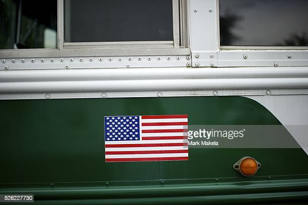 An American flag stick adorns the side of a school bus for a Mitt Romney rally at Exhibit Edge in Chantilly Virginia on May 2 2012