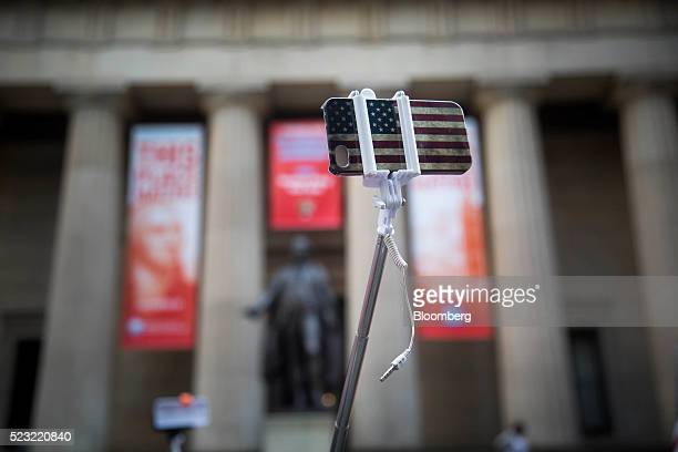 An American flag themed smartphone case on a selfie stick are displayed for sale on Wall Street near the New York Stock Exchange in New York US on...