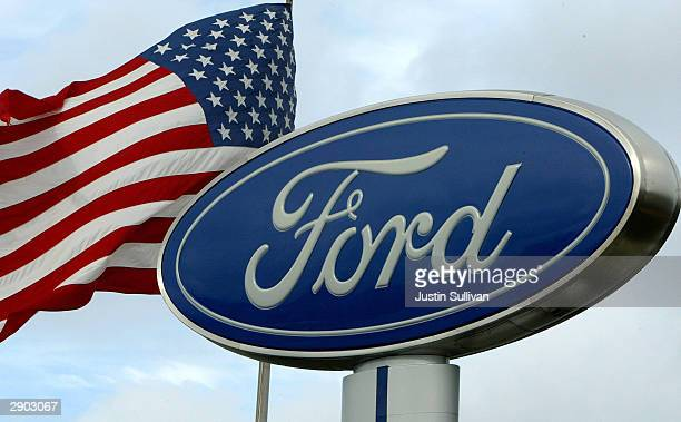 An American flag waves behind a Ford sign at a Ford dealership January 26 2004 in San Bruno California Toyota Motor Corp surpassed Ford Motor Co of...