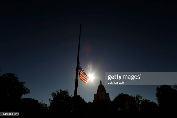 An American flag waves in the wind at half mast outside the State Capitol July 22 2012 in Denver Colorado US President Barack Obama requested all...