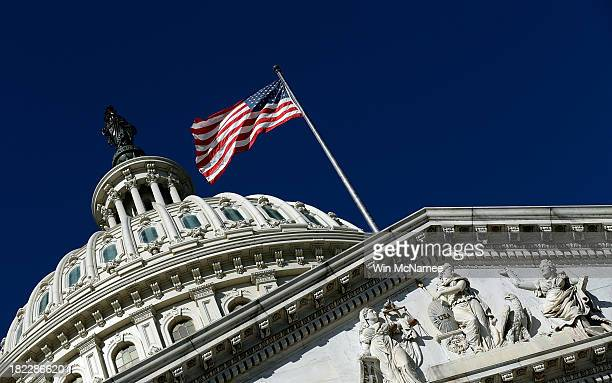 An American flag waves outside the United States Capitol building as Congress remains gridlocked over legislation to continue funding the federal...
