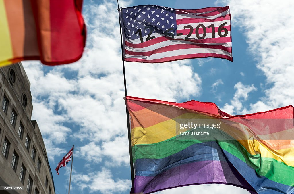 An American flag with the date of the Orlando shotings flies next to rainbow flags and a Union Jack behind as the LGBT community celebrates Pride in London on June 25, 2016 in London, England. Across the city performances and speeches take place as a parade makes it way through the centre ending in Trafalgar Square. 2016 Pride in London comes just two weeks after Omar Mateen shot dead 50 people at Pulse, a gay nightclub in Orlando, Florida.