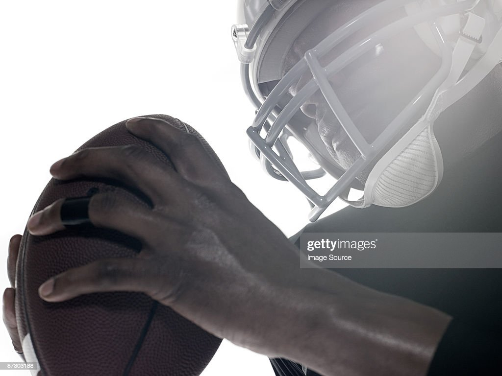 An american football player holding a football : Stock Photo