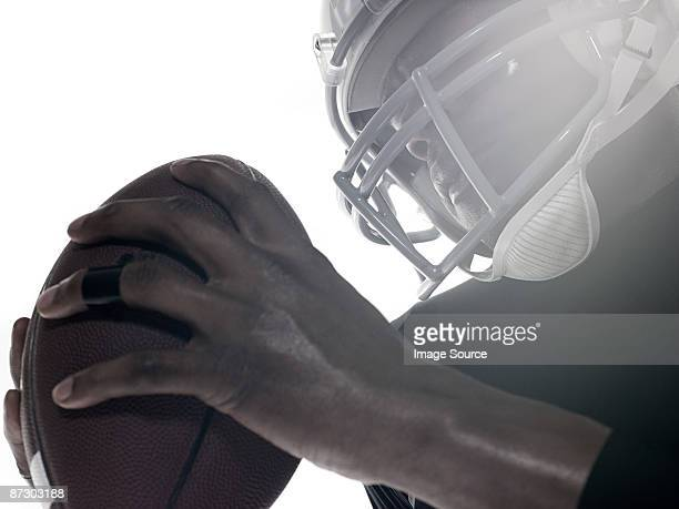An american football player holding a football