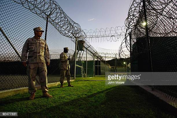 An American guard walks along the exterior of a camp for Chinese Uigur detainees at the US military prison for 'enemy combatants' on October 28 2009...