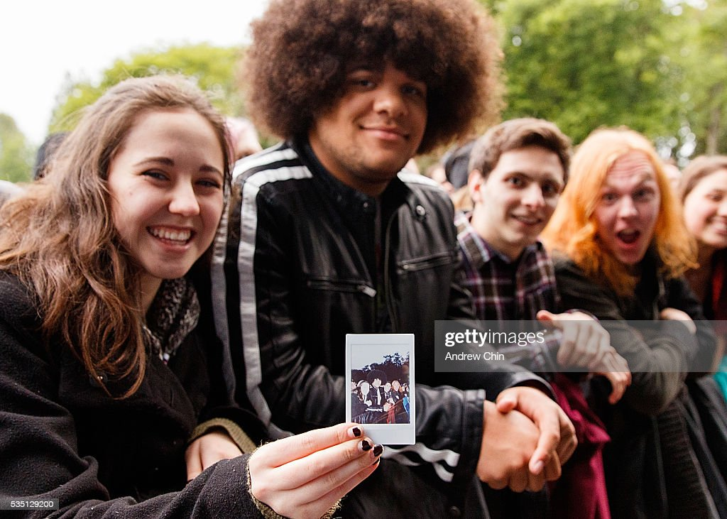 An American guest from Bellingham shows a polaroid group picture while waiting for Alabama Shakes's performance onstage at Deer Lake Park Festival Lawn on May 28, 2016 in Burnaby, Canada.