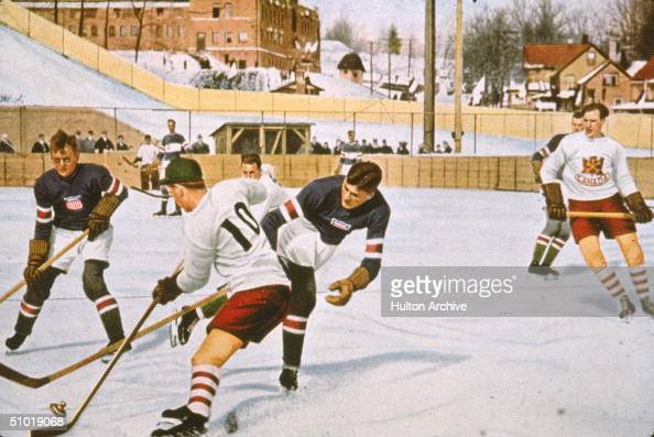 An American hockey play attempts to sweep the puck away from a Canadian in a match between their two countries in the 1932 Lake Placid Olympics early...
