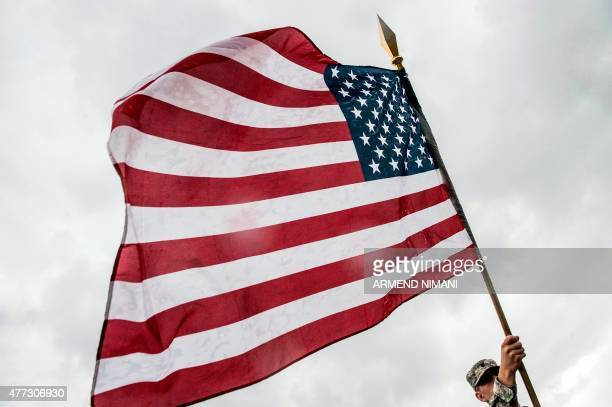 An American Military Cadet holds the US flag during his visit in the town of Ferizaj on June 16 2015 Currently more than 700 US troops are serving in...