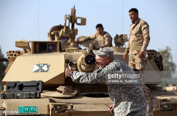 An American military trainer shows Iraqi soldiers how to use a collimator to calibrate the gun barrel of an Abrams tank during a training session at...