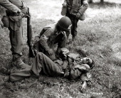 An American Red Cross medic looks at an injured German soldier on the ground July 1944 He is severely wounded in the face and looks dead He was...