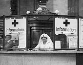 An American Red Cross nurse provides directions and information for enlisted men at Grand Central Station in New York City during World War I circa...
