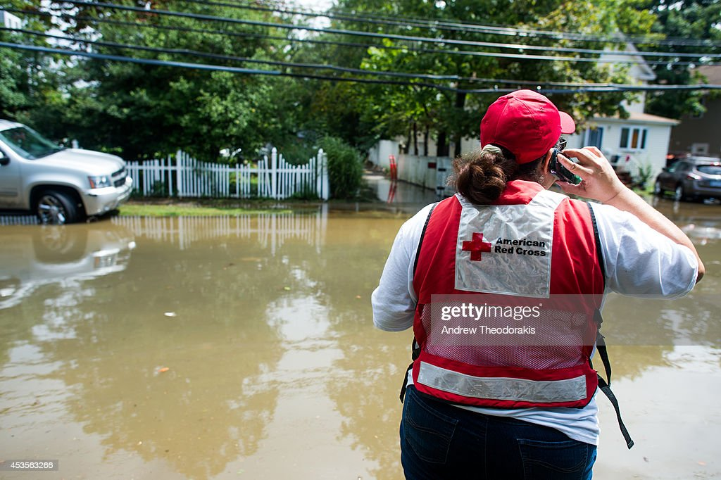 An American Red Cross worker stands on a flooded Brooke Ave following heavy rains and flash flooding August 13, 2014 in Bayshore, New York. The south shore of Long Island along with the tri-state region saw record setting rain that caused roads to flood entrapping some motorists.
