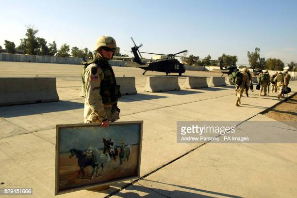 An American soldier carries a painting from Baghdad as he walks to the helipad