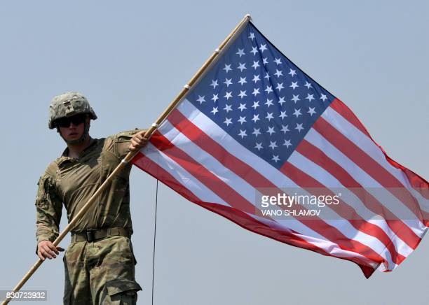 An American soldier carries a US flag during the official closing ceremony of the multinational military exercise 'Noble Partner 2017' at the...