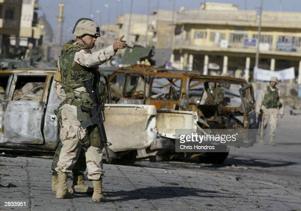 An American soldier directs a coalition soldier in front of wreckage when a car bomb exploded in front of the regional governor's office the previous...