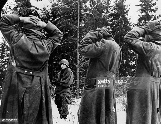 An American soldier holds German prisoners at gunpoint in the snow during WWII's Battle of the Bulge | Location Ardennes region Belgium