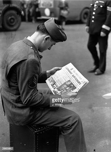 An American soldier in London reads the news of the German surrender at the end of World War II