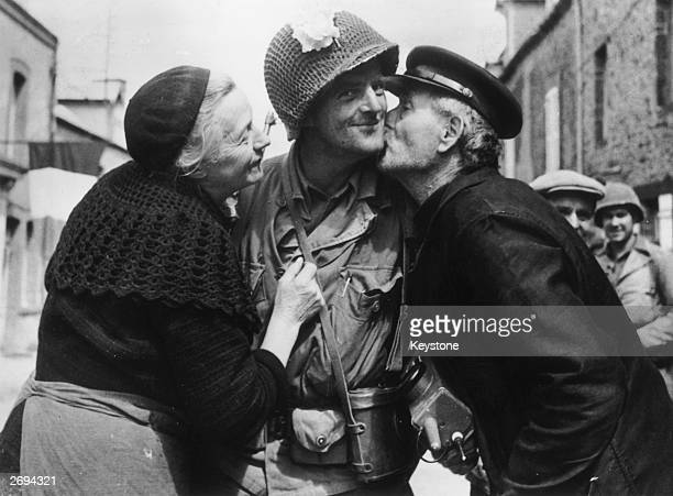 An American soldier is given a warm welcome by an elderly French couple after the town of St Saveur was liberated