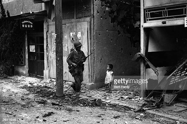 An American soldier patrolling the streets of Inchon after the capture of this key port during the Korean war is watched by a young Korean child...