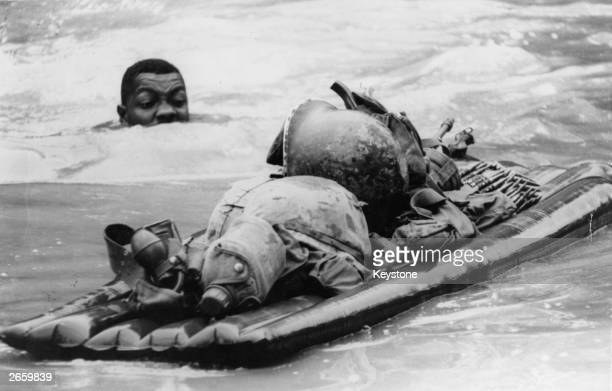 An American soldier pushing his combat gear across a river in Hau Nghia province Vietnam