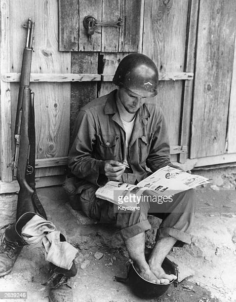 An American soldier relaxes by taking a footbath in a spare helmet whilst reading a magazine during the Korean War