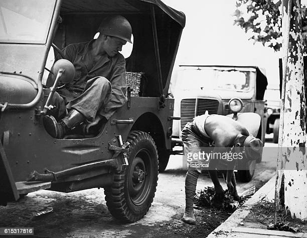 An American soldier sitting in a jeep watches a former Japanese soldier clean gutters in Yokohama Japan ca 1945