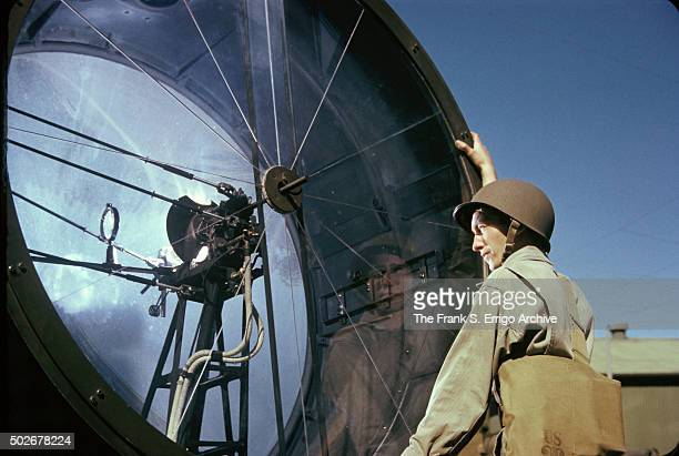 An American soldier stands angles a searchlight during training early to mid 1940s Seachlights formed part of a system of antiaircraft defense