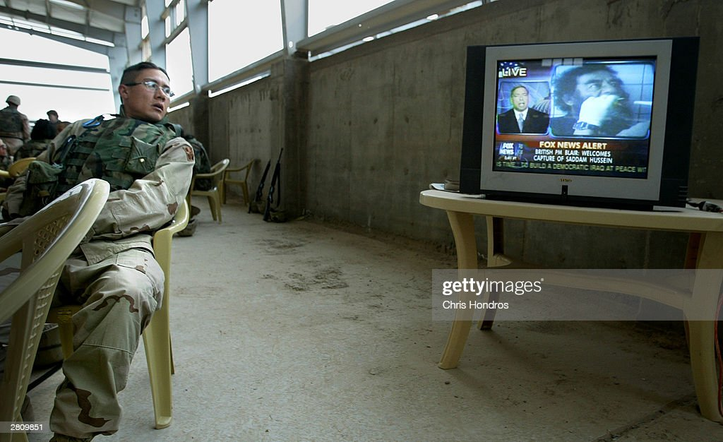 An American soldier watches news of the capture of Saddam Hussein on a chow hall television on a base December 14, 2003 near Samarra, Iraq. Iraq's notorious dictator was captured in a raid near Tikrit.