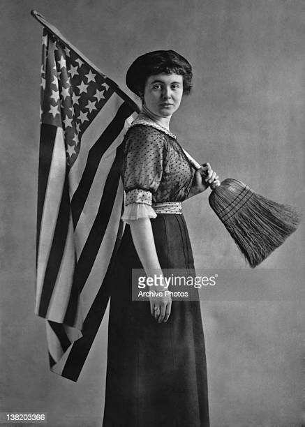 An American suffragette carrying a US flag attached to a broom handle circa 1917