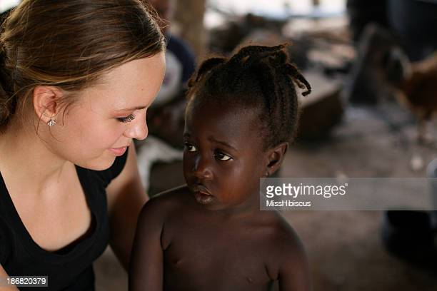 An American teenage girl with a young African girl
