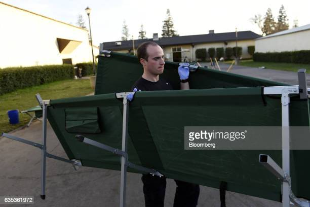 An Americorps volunteer moves cots at the Silver Dollar Fairgrounds evacuation center in Chico California US on Tuesday Feb 14 2017 State officials...