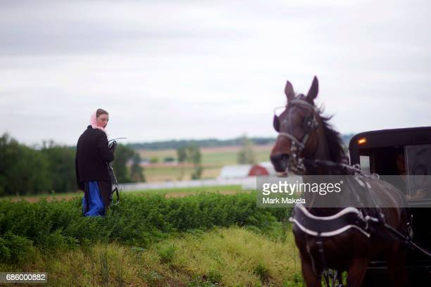 An Amish girl walks in planted fields while a buggy passes by before a planned KKK rally May 20 2017 in Quarryville Pennsylvania A Marylandbased...