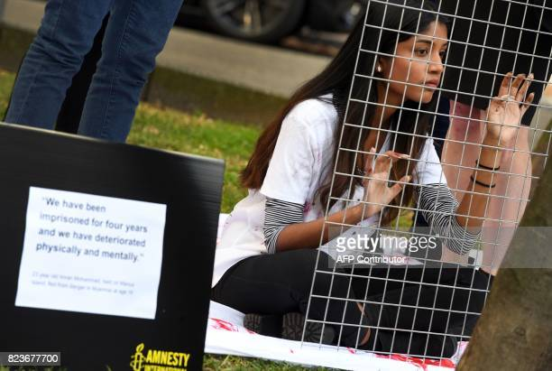An Amnesty International activist protests outside the Spanish corporate giant Ferrovials Australian headquarters in Sydney on July 28 2017 Ferrovial...