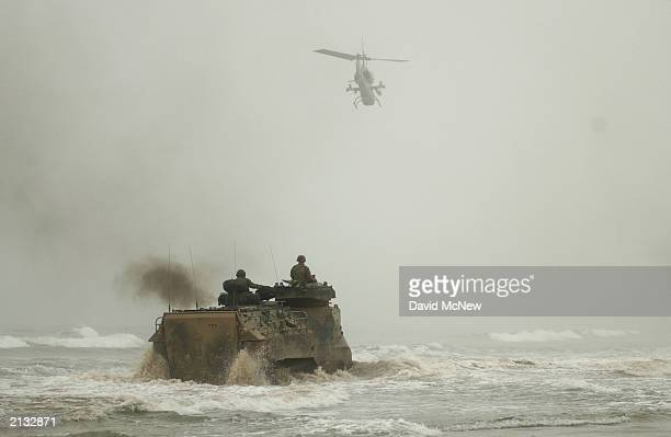 An amphibious assault vehicle navigates choppy seas as an attack helicopter flies overhead during the return of US Marines with 1st Battalion 11th...
