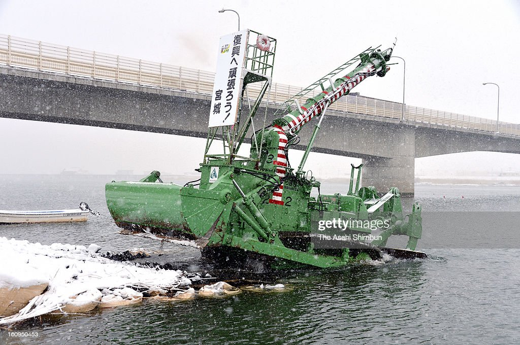 An Amphibious bulldozer fortifies the foundations of a bridge across the Natorigawa riveron February 6, 2013 in Sendai, MIyagi, Japan. A snorkel-equipped bulldozer designed for shallow coastal and river work has been cranked into life again after sitting idle for 20 years.