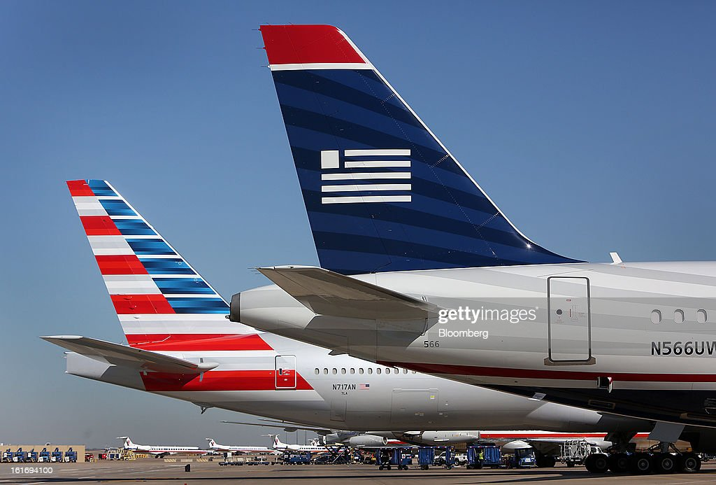 An AMR Corp.'s American Airlines airplane, left, and a US Airways Group Inc. airplane sit parked at a gate at Dallas Fort Worth Airport in Fort Worth, Texas, U.S., on Thursday, Feb. 14, 2013. US Airways Group Inc., spurned in three prior merger attempts, will combine with bankrupt AMR Corp.'s American Airlines in an $11 billion all-stock deal to create the world's largest carrier. Photographer: Mike Fuentes/Bloomberg via Getty Images