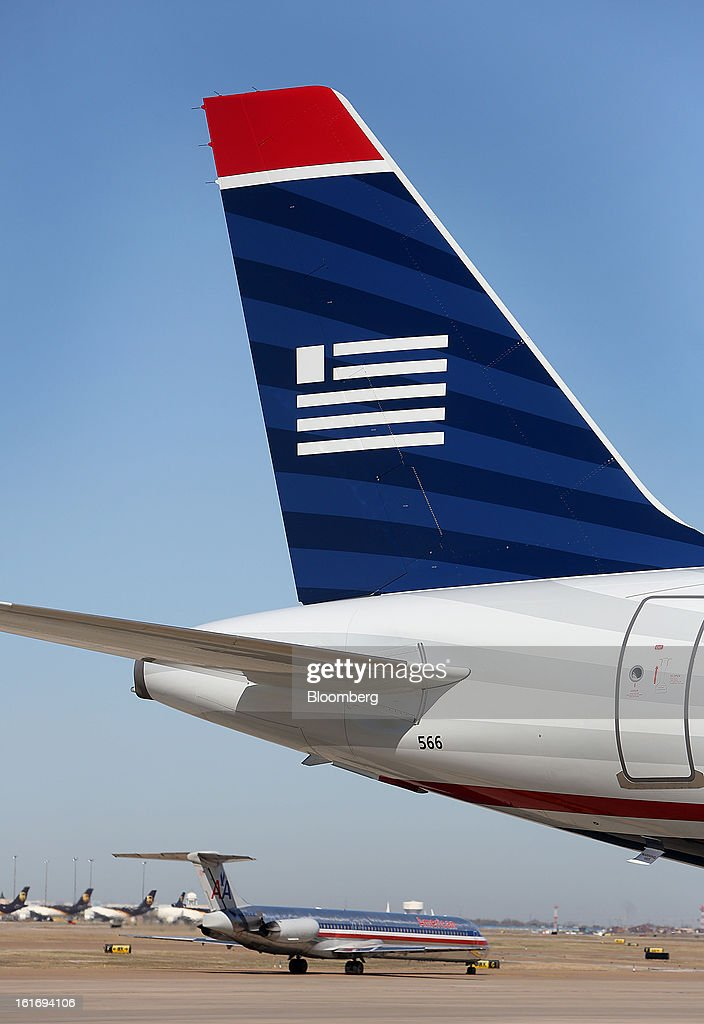 An AMR Corp.'s American Airlines airplane taxis on the runway, at rear, while a US Airways Group Inc. jet sits parked at a gate at Dallas Fort Worth Airport in Fort Worth, Texas, U.S., on Thursday, Feb. 14, 2013. US Airways Group Inc., spurned in three prior merger attempts, will combine with bankrupt AMR Corp.'s American Airlines in an $11 billion all-stock deal to create the world's largest carrier. Photographer: Mike Fuentes/Bloomberg via Getty Images