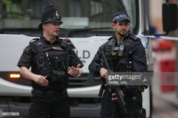 An amred police officer stands on duty near to London Bridge in London on June 4 as police continue their investigations following the June 3 terror...