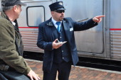 An Amtrak conductor assists a passenger boarding the Southwest Chief at the Amtrak station in Lamy New Mexico The train runs daily between Los...