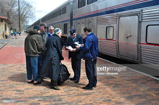 An Amtrak conductor assists passengers boarding the Southwest Chief at the Amtrak station in Lamy New Mexico The train runs daily between Los Angeles...