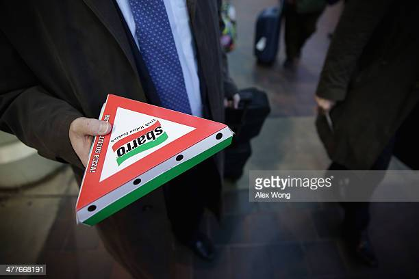 An Amtrak passenger holds a box of Sbarro pizza as he is about to board a train at the Union Station March 10 2014 in Washington DC Sbarro filed for...