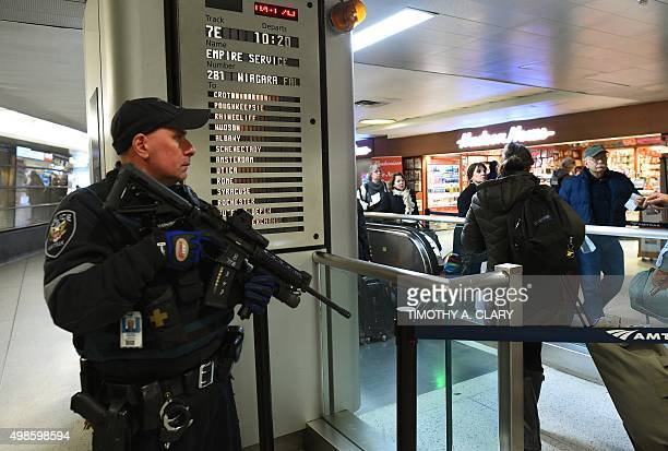 An Amtrak Police officer watches passengersas they board a train at Penn Station on November 24 2015 in New York After a string of terror attacks in...