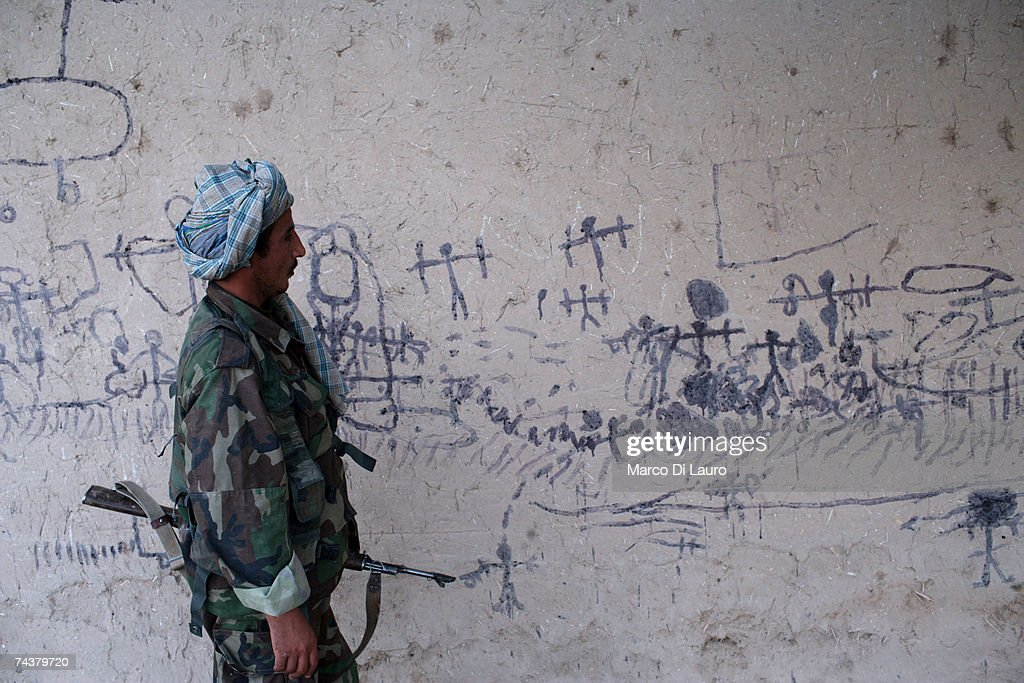 An ANA (Afghan National Army) Soldier looks at graffiti most likely draw by Afghan children depicting a battle between Taliban and ISAF forces on a wall of a village during 'Lastay Kulang' Operation' on June 1, 2007 in Sangin Valley, Helmand Province, Afghanistan. British troops from The Inkerman Company, 1st Battalion Grenadier Guards, part of ISAF Task Force Helmand, are mentoring the Afghan National Army while conducting security operations on behalf of the Government of Afghanistan in Helmand Province.