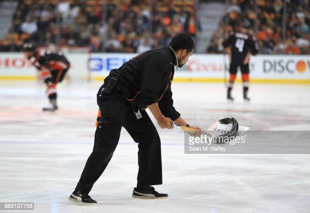 An Anaheim Ducks ice crew member shovels a catfish that was thrown on the ice prior to Game Two of the Western Conference Final between the Nashville...